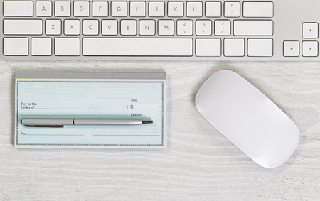 checkbook: Image of partial keyboard blank checkbook silver pen and mouse on white desktop. Layout in horizontal format. Stock Photo