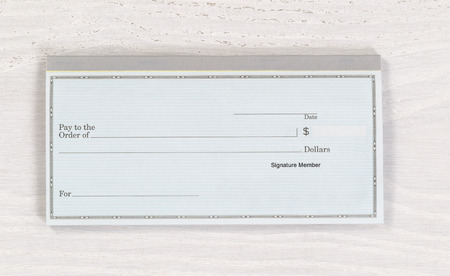 checkbook: Close up of blank checkbook on white wooden desktop. Layout in horizontal format.