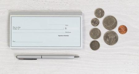 chequera: Cierre plano de la pluma de plata y monedas chequera en blanco en el escritorio de madera blanca. Disposición en formato horizontal.