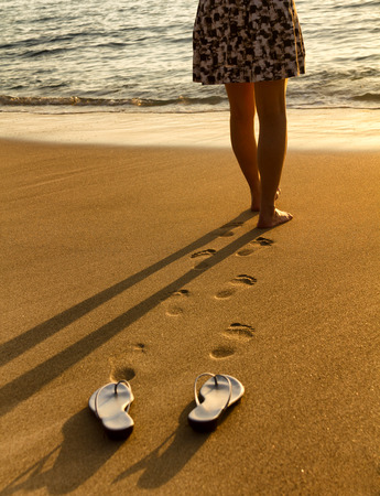 waist down: Woman waist down walking barefoot into Pacific Ocean during golden sunset. Focus on foot prints with sandals in forefront. Stock Photo