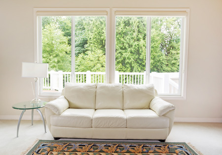Clean family room with white leather couch and large windows showing bright green trees in background.