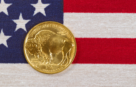 issued: United States Mint issued American Buffalo coin, fine gold, on USA flag. Stock Photo