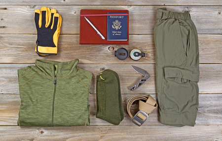 camping equipment: Clothing for hiking organized on rustic wooden boards