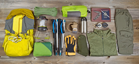 camping equipment: High angled view of organized hiking gear placed on rustic wooden boards in rectangle format.