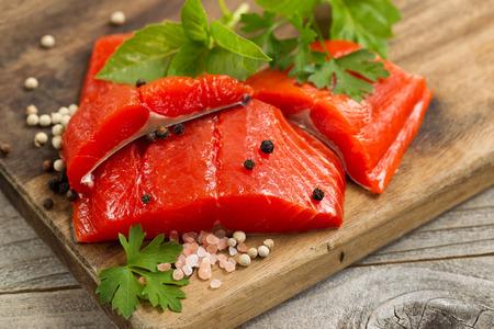 カッティング ボード、海の塩、ハーブの新鮮な明るい赤い銅川鮭切り身の上から見るショット。