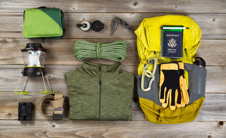outdoor: High angled view of organized hiking gear for climbing placed on rustic wooden boards.