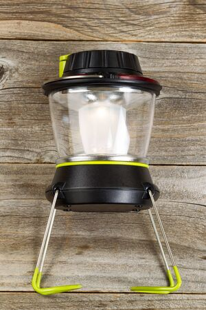 vertical orientation: Vertical orientation of an outdoor new battery lantern on rustic wooden boards. Stock Photo