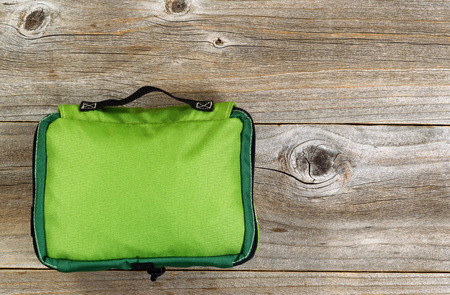 travel bag: Top view shot of a weather proof nylon medical kit bag for outdoor travel on rustic wooden boards. Stock Photo