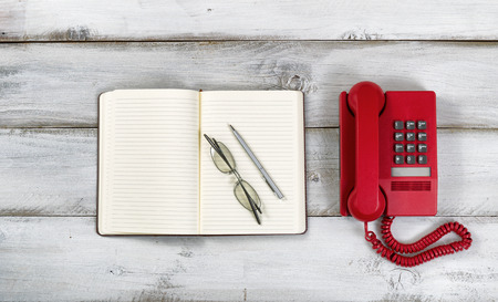 Vintage red phone, notepad, pen and reading glasses on rustic white wooden boards. High angled view.