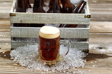 bottled beer: Frosty glass mug of dark beer, focus on front, with vintage crate filled with bottled beer and crushed ice on rustic wooden boards.