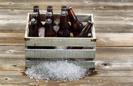 Vintage crate filled with bottled beer and crushed ice on rustic wooden boards.