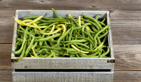 ejotes: Old crate filled with freshly picked green and yellow beans on rustic wooden boards.