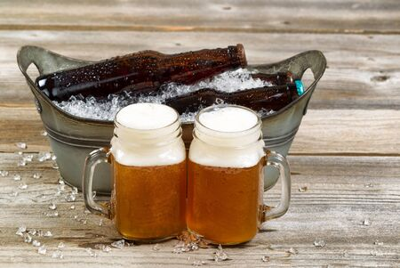 beer bucket: Two pints of frosty cold beer with metal bucket and ice in background on rustic wooden boards.