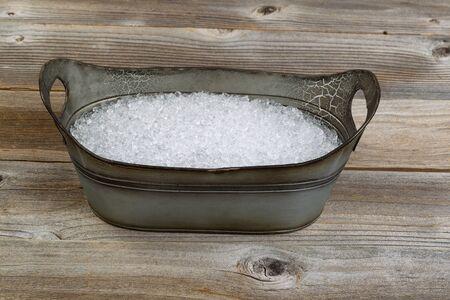 ice crushed: Vintage metalen bad vormige emmer gevuld met crushed ijs op rustieke houten planken.