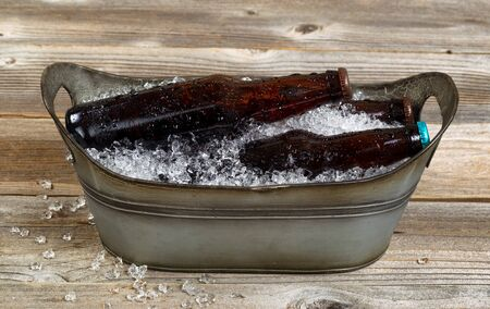 bottled beer: Vintage metal tub shaped bucket filled with crushed ice and bottled beer on rustic wooden boards.