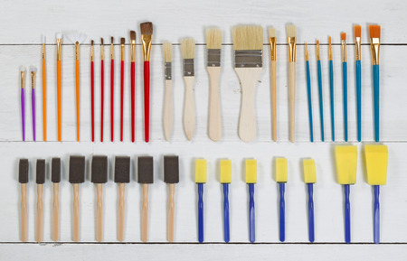angled view: High angled view of brand new paint brushes and applicators organized on white wood. Layout in horizontal format.