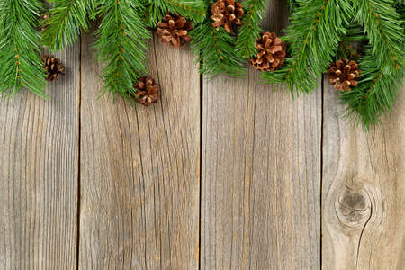 Christmas border with pine tree branches and cones on rustic wooden boards.