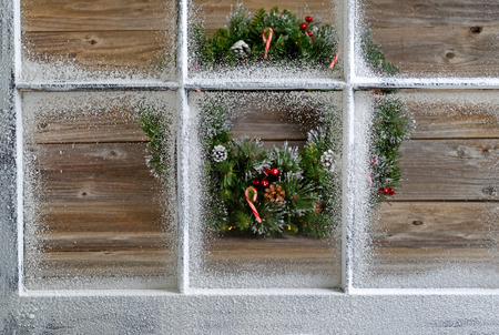 snow covered: Snow covered window with decorative Christmas wreath on rustic wooden boards in background. Focus on window glass and sills.