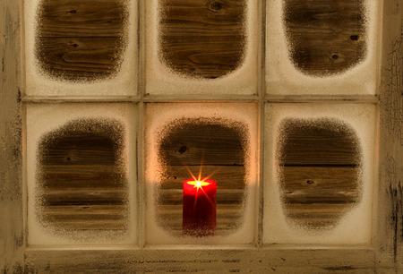 velas de navidad: Nieve ventana y brillante vela roja en el fondo de madera rústica cubierta.