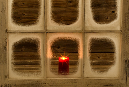 Snow covered window and glowing red candle on rustic wood background.