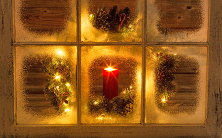 winter window: Glowing candle in window during evening with warmness inside of home. Stock Photo