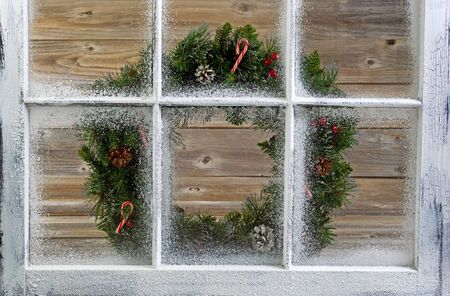 snow covered: Snow covered window with decorative Christmas wreath on window with rustic wood in background.