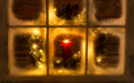 Snow covered window with glowing candle and decorative Christmas wreath on window with rustic wood in background.