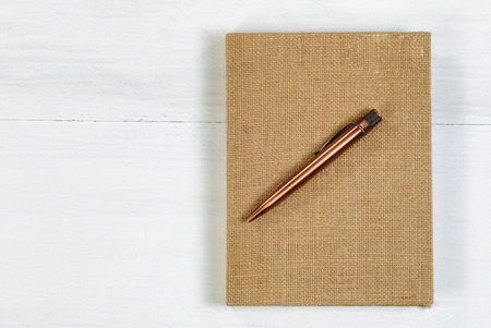 vintage document: Vintage metal pen and burlap covered notepad on white wooden desktop.