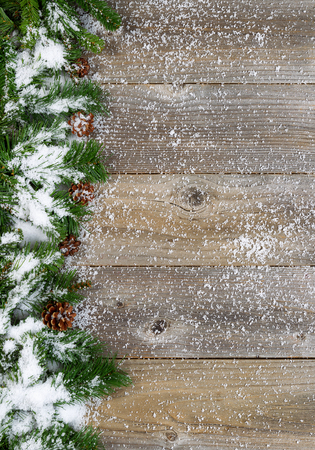 vertical format: Christmas border with pine tree branches, cones and snow on rustic wooden boards. Layout in vertical format.