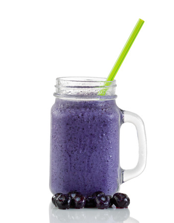 Frosted blueberry smoothie in jar glass with whole berries and green straw isolated on white with reflection. Imagens