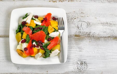 food healthy: Top view image of a healthy fresh salad on plate with rustic white wooden boards underneath.