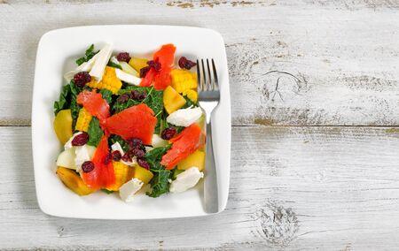 salad in plate: Vista superior de la imagen de una ensalada fresca y saludable en la placa con r�sticas tablas de madera blanca por debajo.