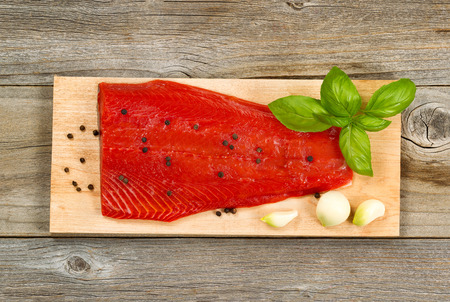 red salmon: Top view shot of fresh red salmon fillet on cedar cooking board with peppercorn, garlic and basil. Aged wood underneath.