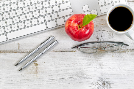 Red apple, coffee, reading glasses and silver pens next to computer keyboard with rustic white desktop underneath. Banque d'images
