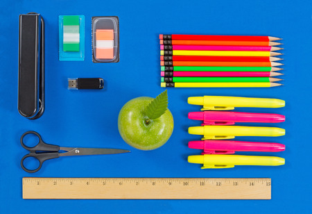 consisting: Office or back to school supplies consisting of a green apple, highlight markers, stapler, thumb drive, ruler, scissors, tab markers and colorful pencils on blue background.