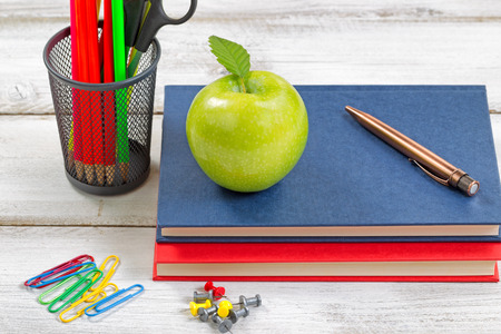 pluma y papel: A healthy green apple, books, pen, paper clips, tacks and container with supplies on top of white desktop. Education concept. Foto de archivo
