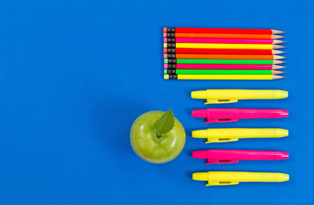 highlight: Office or back to school supplies consisting of a green apple, highlight markers and colorful pencils on blue background. Stock Photo