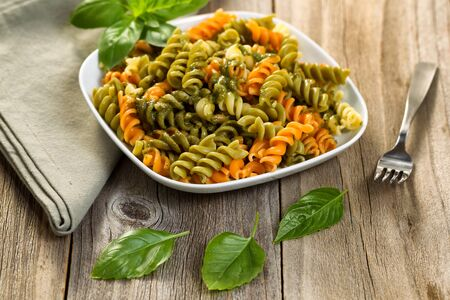 dish: Fresh pasta with and fusilli noodles and basil pesto, selective focus on front part of dish.