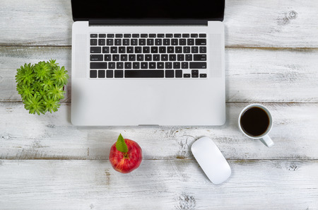 Red apple, coffee, mouse, plant and computer on top of laptop with rustic white desktop. Stock Photo