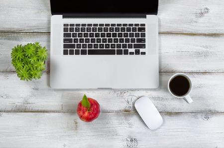 manzana: Red de manzana, café, ratón, planta y equipo en la parte superior de la computadora portátil con el escritorio blanco rústico.