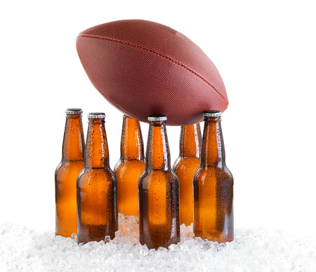 Six pack of bottled beer holding up American Football isolated on white background