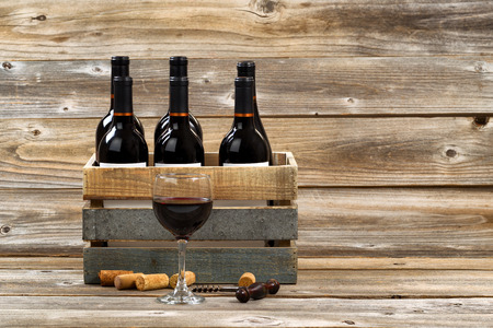 box: Glass of red wine with full bottles in wood crate, old corkscrew and used corks on rustic wooden boards.