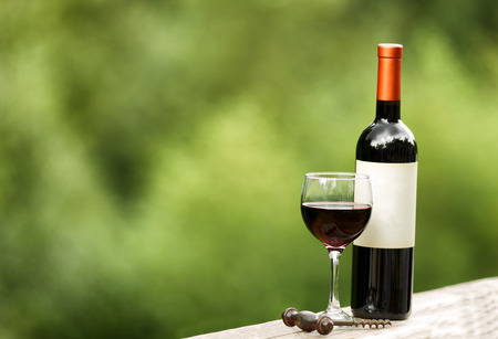 Glass of red wine with full bottle and corkscrew on rustic wood outdoors. Selective focus on front of wine glass with shallow depth of field on horizontal layout.