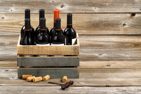 Red wine bottles in wooden crate with old corkscrew and used corks on rustic wooden boards.
