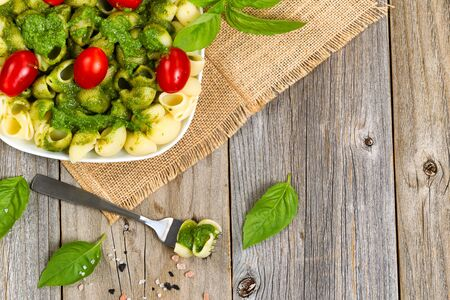 pasta: Top view of basil pesto with shell shaped pasta and cherry tomatoes on rustic wood.