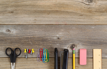 office desk: Top view of partial business and education supplies on rustic wood.