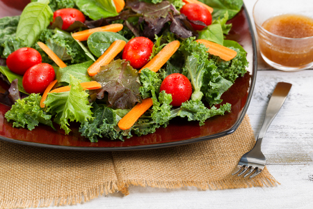 Close up front view, selective focus on lower right corner of plate, of fresh green salad with carrots, cherry tomato, basil, baby kale, and lettuce on rustic white wooden table. Stock Photo