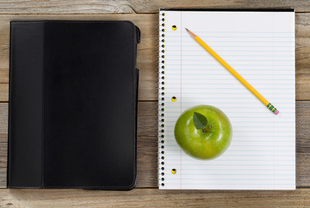 school work: Top view of green apple, notepad, pencil and notebook on rustic wood.