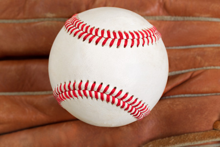 mitt: Close of baseball, selective focus on center, with leather mitt in background. Format in filled frame layout. Stock Photo