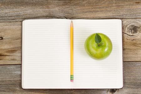 manzana verde: Vista superior de la manzana verde, la libreta abierta con el lápiz en el centro en la madera rústica.